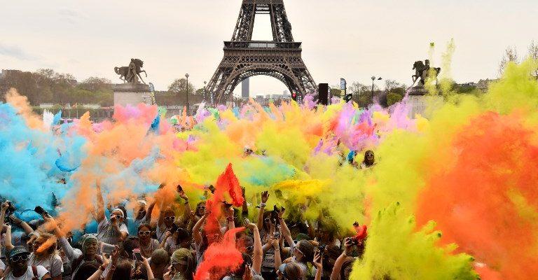 Los corredores celebran bajo polvo de color terminando sus cinco kilómetros en el Color Run 2018 en la Torre Eiffel en París el 15 de abril de 2018. / PH: Christophe Simon - AFP.