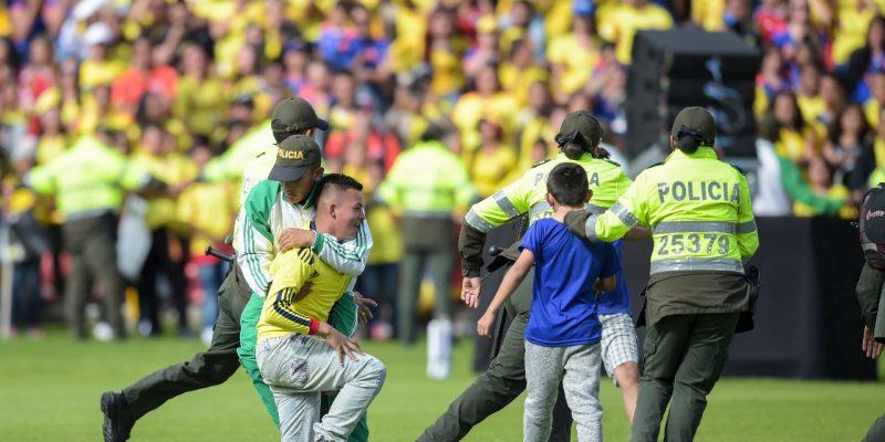 Los fanáticos son detenidos por la policía cuando ingresan al campo durante la ceremonia de bienvenida de la selección colombiana de fútbol en el estadio El Campín en Bogotá el 5 de julio de 2018, luego de su participación en la Copa Mundial de la FIFA. Inglaterra venció a Colombia en una dramática tanda de penales en Moscú el 3 de julio para alcanzar los cuartos de final de la Copa del Mundo. FOTO: Raúl ARBOLEDA / AFP