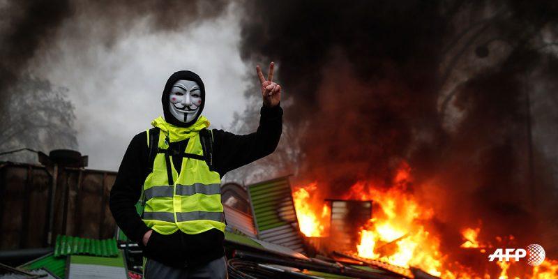FRANCIA-SOCIAL-POLITICS-DEMO-FUEL Un manifestante que lleva una máscara de Guy Fawkes hace el signo de la victoria cerca de una barricada en llamas durante una protesta de chalecos amarillos (Gilets jaunes) contra el aumento del precio del petróleo y los costos de vida, el 1 de diciembre de 2018 en París. Abdulmonam EASSA / AFP